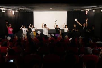舞台挨拶で主題歌を熱唱するキャストやスタッフら(提供)