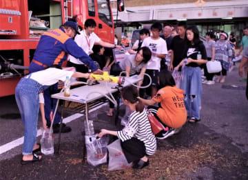 市消防団の水槽車が生活用水を配布。市民が長蛇の列を作った=9日夕、東金市役所