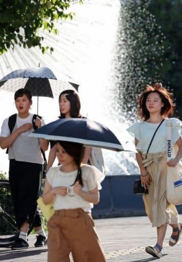 JR岡山駅前を日傘を差して歩く人たち=9日午後4時17分
