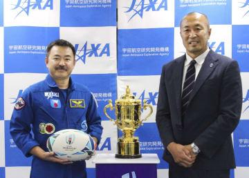 JAXAの筑波宇宙センターで披露されたラグビーW杯日本大会の優勝杯。(左から)宇宙飛行士の星出彰彦さんと元ラグビー日本代表の伊藤剛臣さん=9日午後、茨城県つくば市