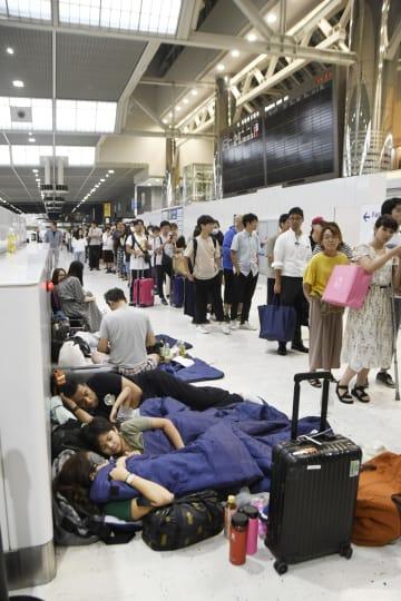 配布された寝袋を使って横になる成田空港の利用客。奥は水や食料の配布を待つ人たち=9日夜