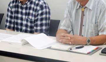 上級生らからのいじめ被害について説明する元防衛大生の男性(左)と父親=横浜市中区