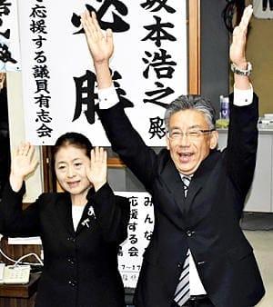 初当選を飾り、万歳する坂本氏(右)と妻玲子さん