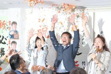 【当選して万歳する竹上氏(中央)=松阪市高町の選挙事務所で】