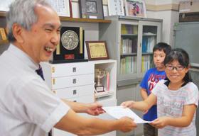 岡田委員長から表彰状を受け取る児童(白老小)
