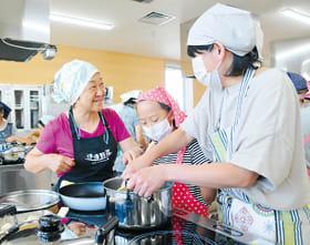 参加者と笑顔で交流し料理の魅力を伝える佐々木さん(左)