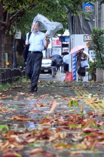台風の影響で風雨が強まる中、通勤する人たち=9日午前7時55分、宇都宮市本町