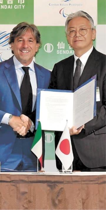 協定書を手に握手するスターラ事務総長(左)と天野局長