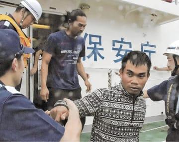 釧路港に到着した海上保安庁の巡視艇から下りる、救助された第18鴻丸の乗組員(中央の2人)=8日午後、北海道釧路市