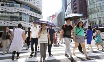 厳しい残暑が続き、日傘を差して歩く人々=10日午後、東京・銀座