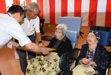 池田市長(左)から祝い状を受ける都城市最高齢の光神ナルさん(右から2人目)ら