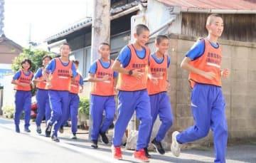 「ランニングパトロール隊」のビブスを着て見守り活動をする倉敷高陸上競技部の生徒たち