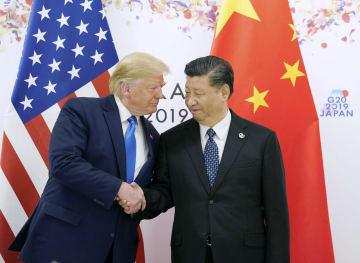 会談を前に握手するトランプ米大統領(左)と中国の習近平国家主席=6月29日、大阪市(ロイター=共同)