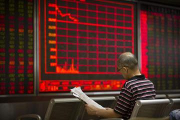 株価の動きを示すモニターの前で新聞を読む投資家=8月、北京(AP=共同)