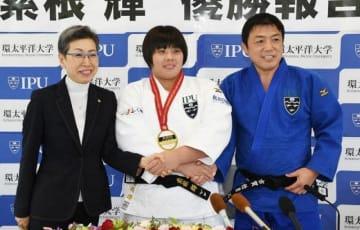 会見で大橋節子学長(左)古賀稔彦総監督(右)と並び、笑顔の素根輝=環太平洋大