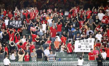サッカーの2022年W杯アジア2次予選の香港―イラン戦の試合前、中国国歌演奏中に客席でデモのスローガンなどを掲げ、ブーイングする人たち=10日、香港(共同)