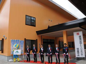 テープカットをして宿泊棟の完成を祝う関係者=下呂市小坂町落合、御嶽濁河高地トレーニングセンター