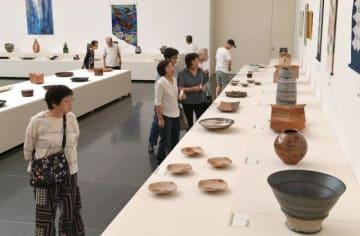 県展工芸部門の会場で、陶芸や染織の力作を楽しむファンら=県立美術館