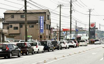 停電が続く千葉県木更津市で、ガソリンスタンドに列を作る車=11日午前