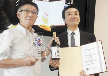 プラチナ賞の賞状や鏡田の4合瓶を手にする村上社長(右)と佐竹知事