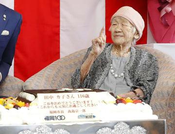 贈られた特大ケーキを前に笑顔の田中カ子さん=11日午後、福岡市