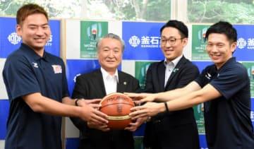 バスケットボールを手に笑顔を見せる水野哲志社長(右から2人目)ら岩手ビッグブルズの関係者と野田武則市長(左から2人目)