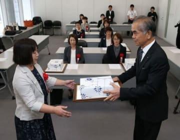松田理事長(右)から表彰状と記念品を受ける受賞者