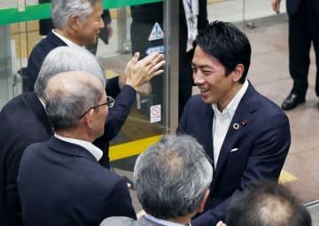 就任記者会見後に、環境省で職員らに迎えられる小泉進次郎環境相(右)=11日夜、東京・霞が関