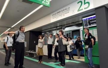 バスから熊本桜町バスターミナルに降り、スタッフの案内を受ける利用客ら=11日午前、熊本市中央区(後藤仁孝)
