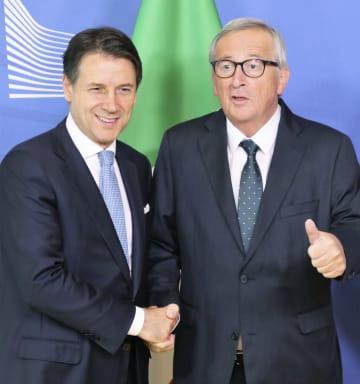 11日、ブリュッセルのEU本部で会談前に握手するイタリアのコンテ首相(左)とユンケル欧州委員長(共同)