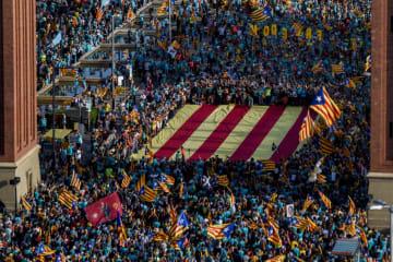 11日、スペイン北東部カタルーニャ自治州の州都バルセロナで、独立派の巨大な旗を掲げ行進するデモ参加者(ゲッティ=共同)