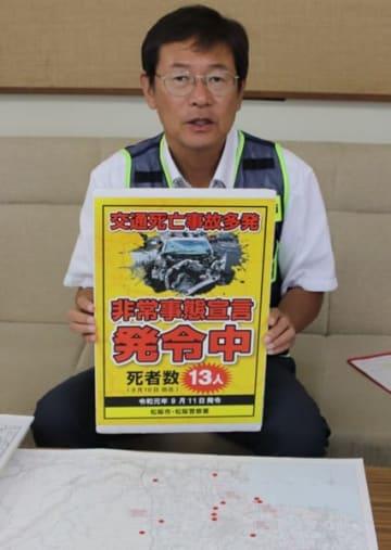 【交通死亡事故多発非常事態宣言のポスターを示す竹上市長=松阪市役所で】