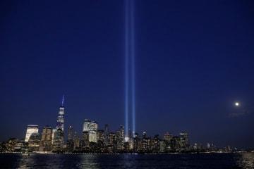 11日、米ニューヨークで、ライトアップされた高層ビルを象徴する2本の柱(ロイター=共同)
