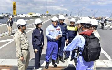 被害状況の説明を受ける赤羽国交相(左から3人目)=12日午前、横浜港