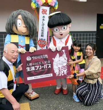 「水木しげる記念館」の無料入館券を贈られた、400万人目の入館者御堂有香さん(右端)=12日午前、鳥取県境港市