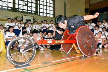 固定した競技用車いすで、高速走行する様子を見せる永尾嘉章さん=山形市・山形一中