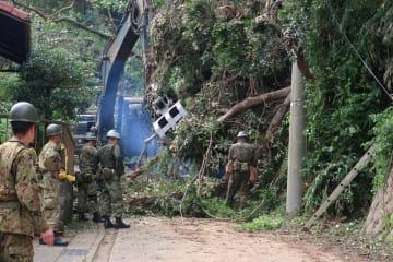 重機も使い、倒木を撤去する自衛隊員=11日午前9時25分ごろ、鎌倉市二階堂