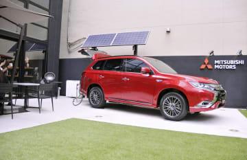 三菱自動車のブランド発信拠点に展示された「アウトランダーPHEV」と給電システム=12日、東京・銀座