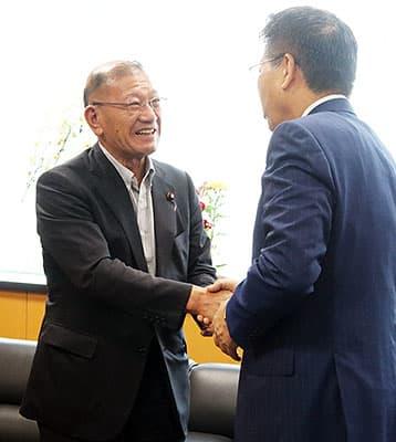 引き継ぎ式で衛藤氏(右)と握手する宮腰氏=内閣府