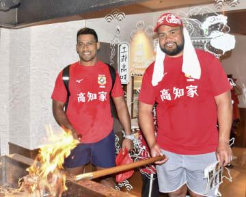 カツオのわら焼き作りを体験するラグビーW杯トンガ代表の選手=12日、高知市