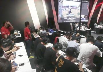 NTTドコモのブースで開かれた、多人数が同時に対戦できるゲームイベント=12日午後、千葉市の幕張メッセ