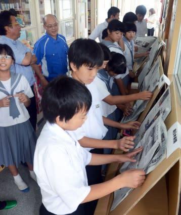 段ボールで手作りした閲覧台で新聞を読む生徒たち=日置市伊集院の土橋中学校