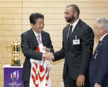 ラグビー日本代表のリーチ・マイケル主将(中央)と握手する安倍首相=12日午後、首相官邸