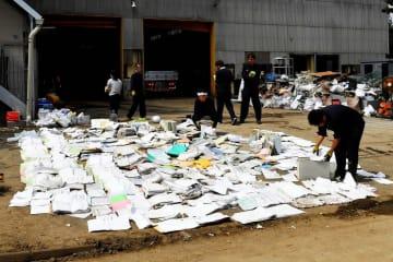 浸水してぬれた書類を並べる工場関係者=11日、横浜市金沢区