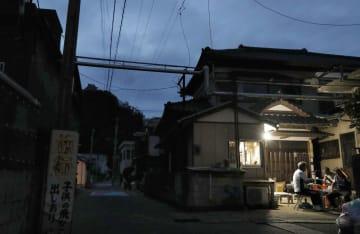 停電が続く千葉県鋸南町では、住民らが工面したガソリンと発電機でともした明かりに人々が集まっていた=12日夕