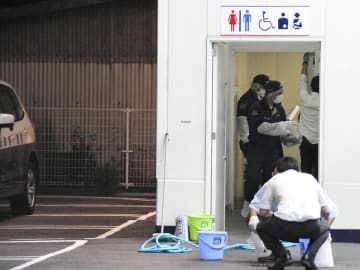 女性が刺された現場付近を調べる捜査員=12日午後7時9分、関市東新町、ゲンキー関東新店