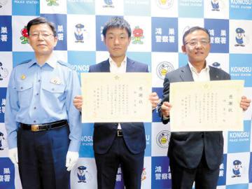 踏切内にたたずむ若い女性を救助した林秀行さん(右)と林宏俊さん(中央)親子。左は山口正人署長=鴻巣署