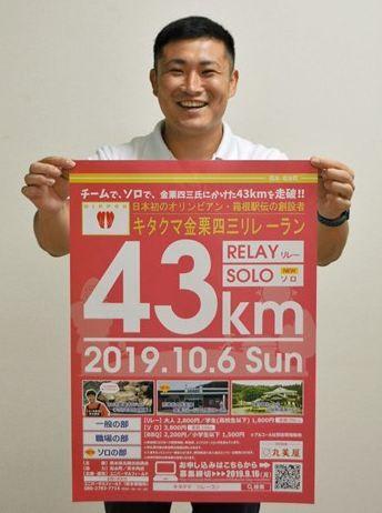 「キタクマ金栗四三リレーラン」のポスターを持つ和水町職員=同町