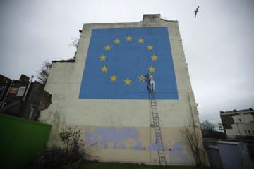 EU旗の星を消そうとする人を描いたバンクシーの壁画=1月7日、英南東部ドーバー(AP=共同)