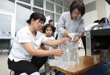 台風15号の影響による断水で、給水所に水をくみにきた親子ら=13日午前、千葉県南房総市